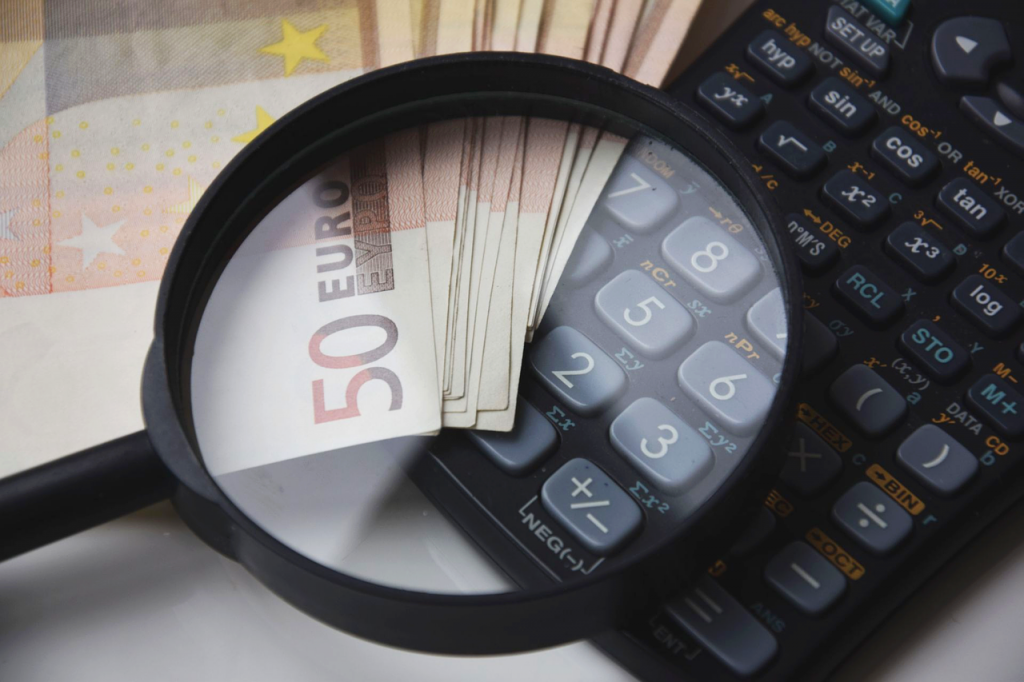 a magnifying glass, a calculator and money - everything you need to calculate overall moving costs