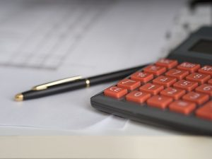 A calculator and a pen you will use to prepare your budget for moving to Hong Kong.