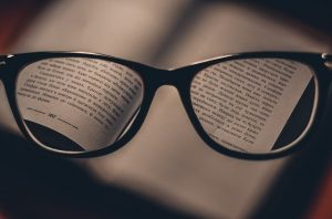 Looking to a book through glasses.
