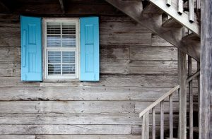 A blue window on a wooden house.