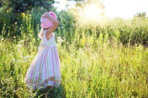 Little girl, standing in grass.