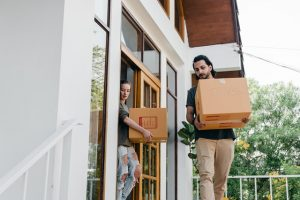 People carrying boxes after buying a property.