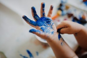 Child's hand dipped in blue paint.