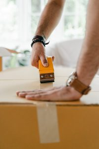 a man sealing the cardboard box with tape