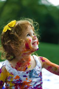 A little girl playing with water colors that are all over her face and clothes.
